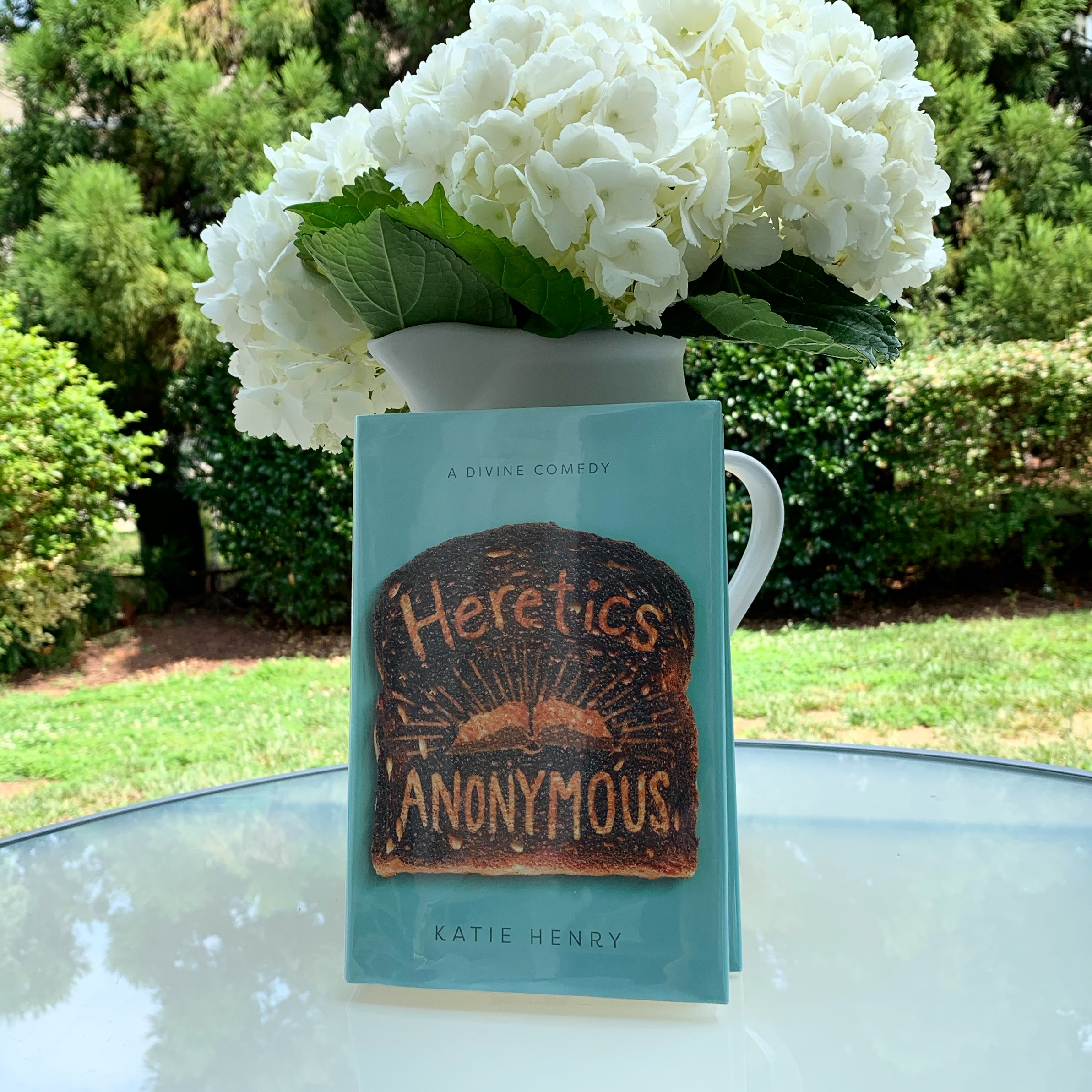 Heretics Anonymous by Katie Henry library book and vase of white hydrangeas