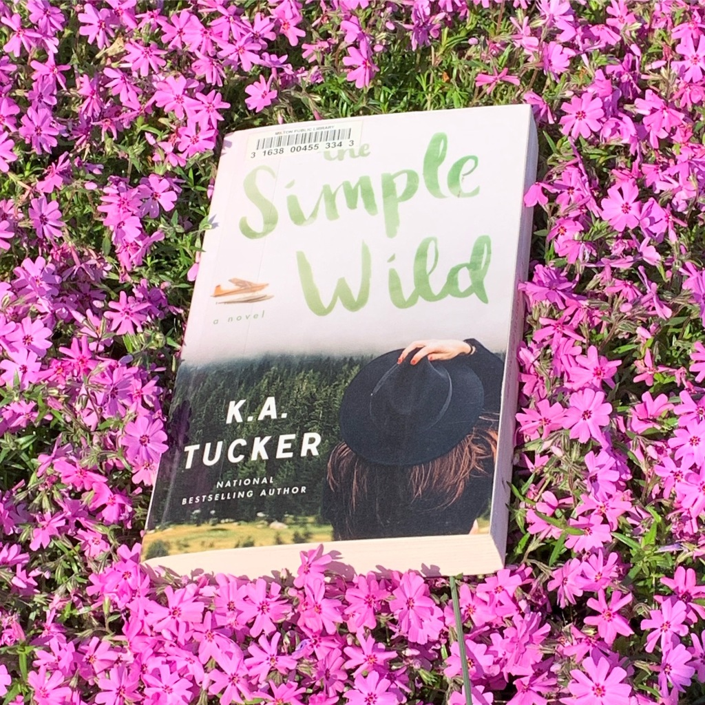 The Simple Wild book surrounded by purple flowers