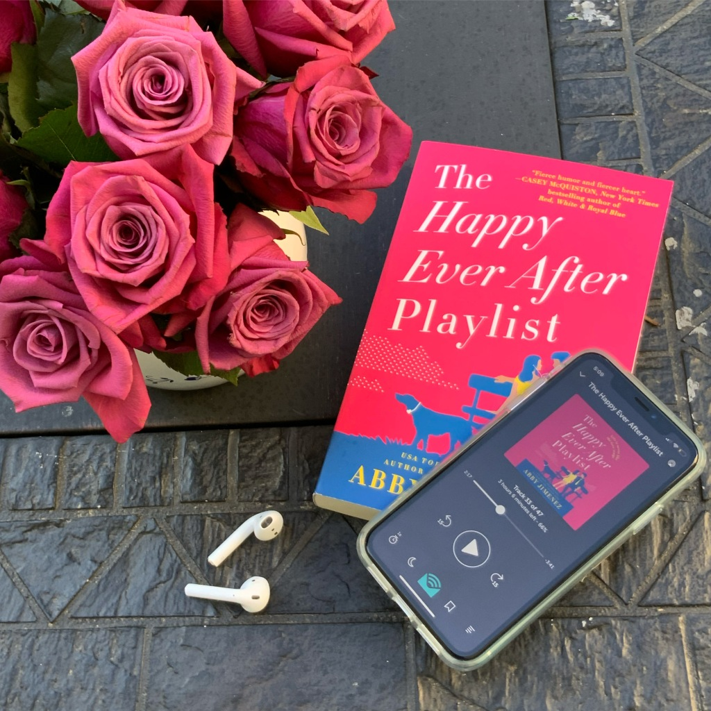 The Happy Ever After Playlist book and audiobook on phone with pink roses