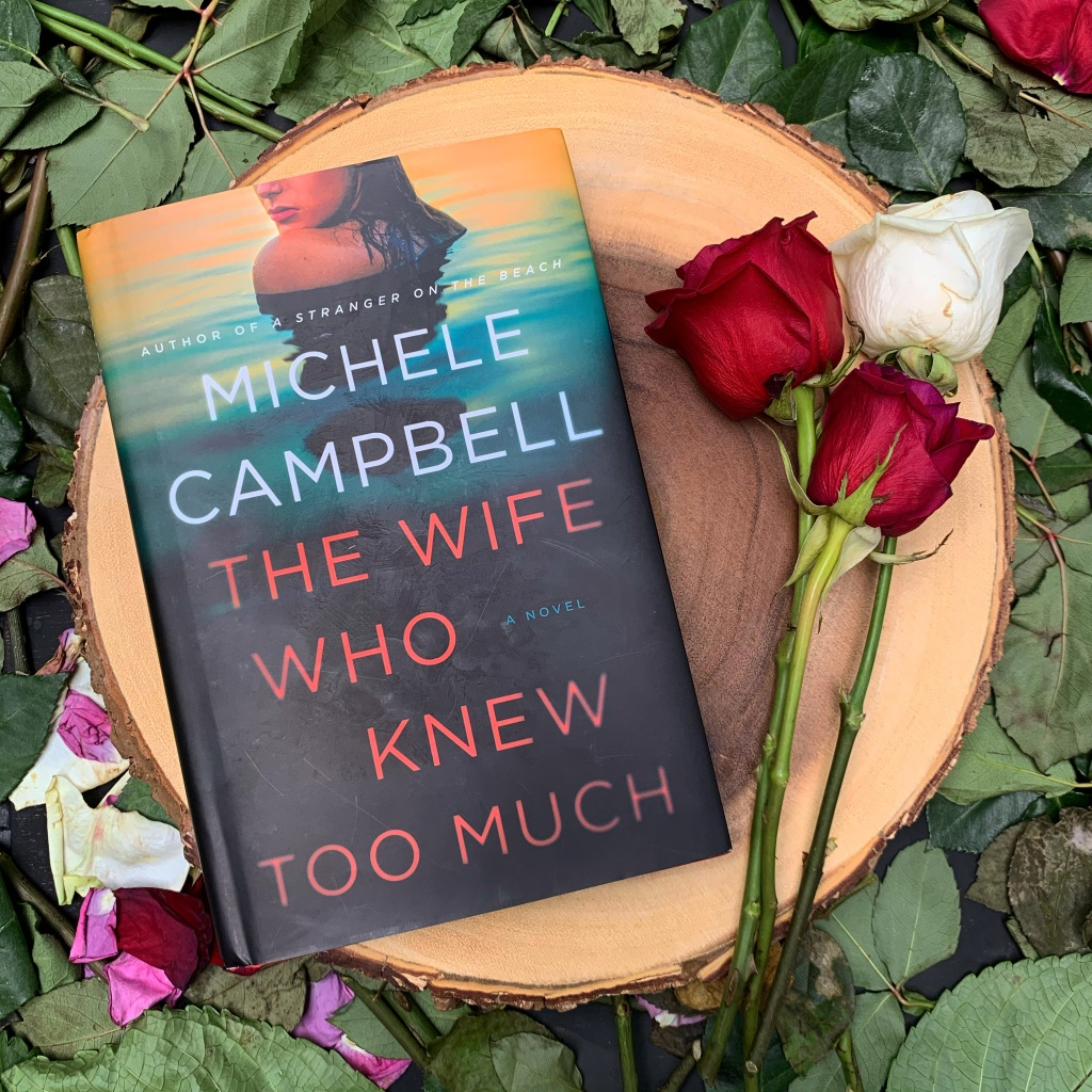 The Wife Who Knew Too Much by Michele Campbell hardcover on wood slab with white and red roses