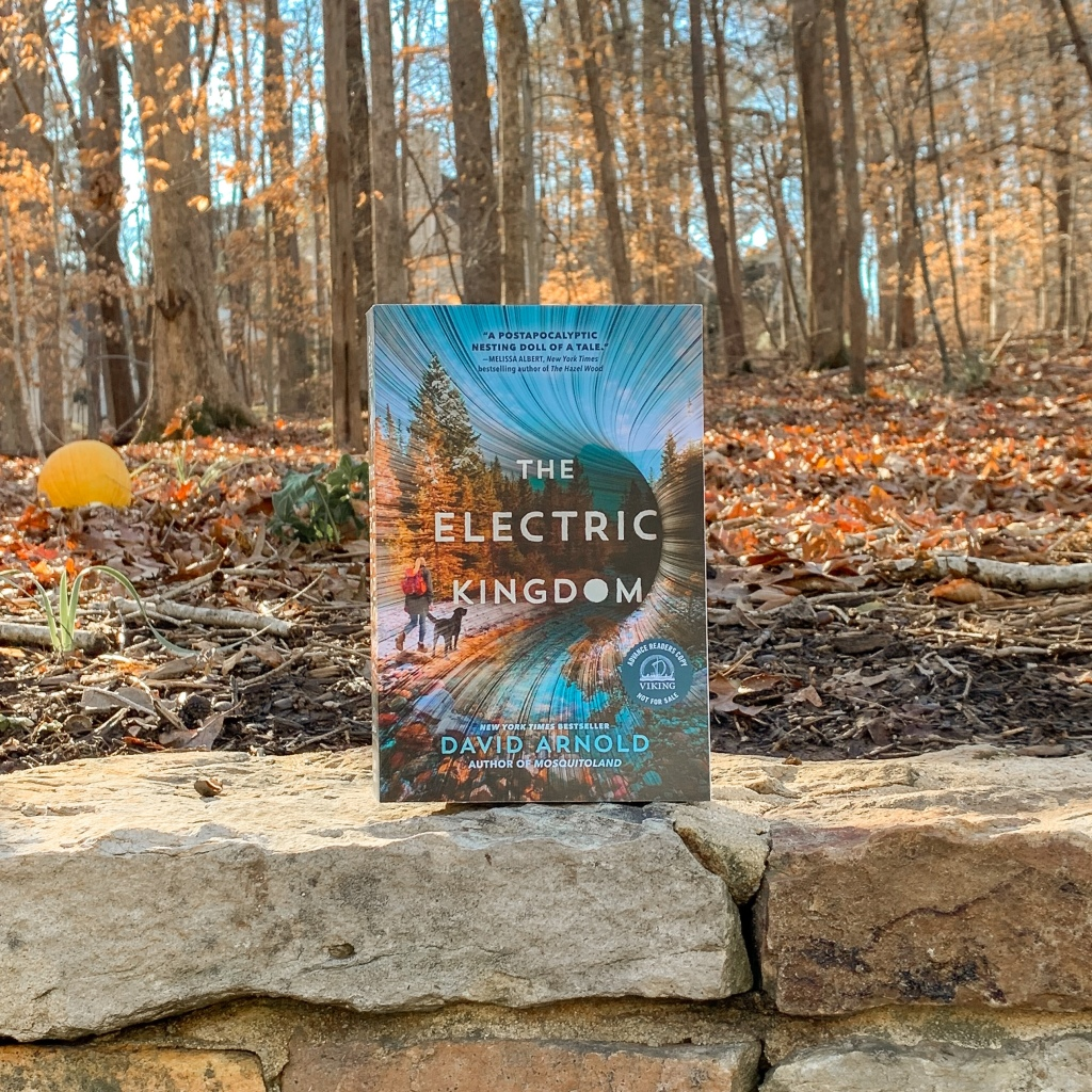 Photo of The Electric Kingdom by David Arnold paperback in the woods