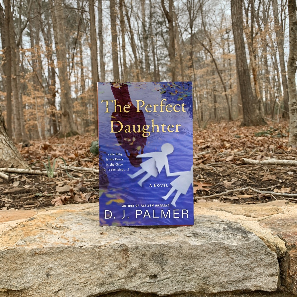 The Perfect Daughter by DJ Palmer hardcover book in the woods with gold leaves