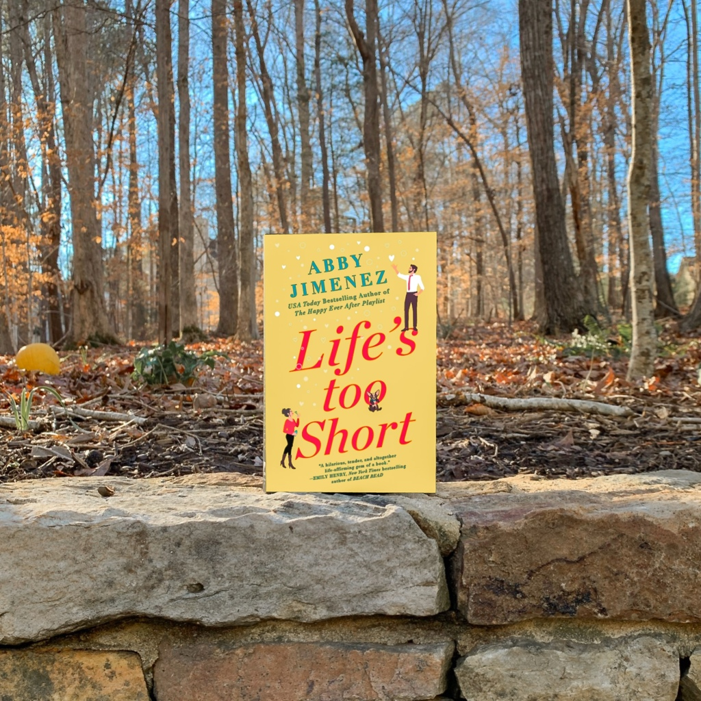 Life's Too Short by Abby Jimenez paperback book in the woods surrounded by gold leaves