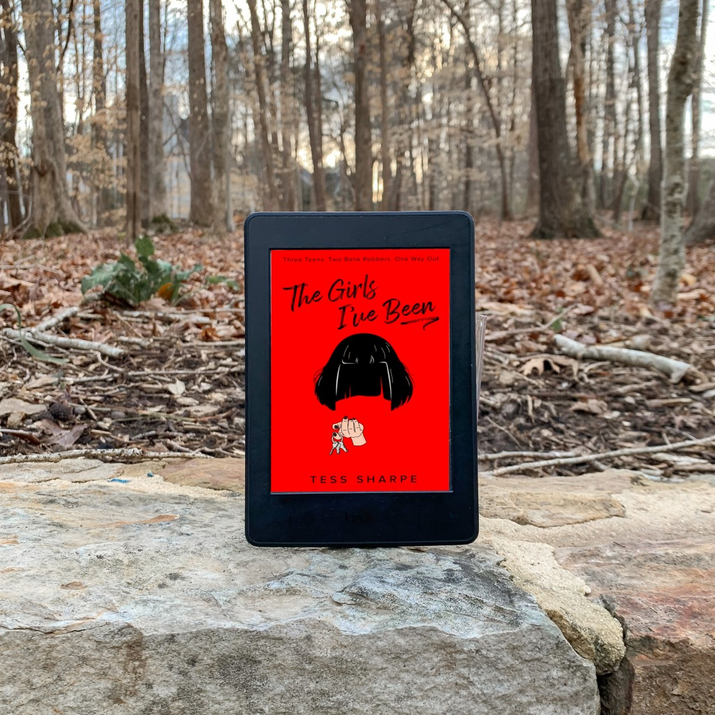 Photo The Girl's I've Been by Tess Sharpe eARC on Kindle paperwhite surrounded by trees