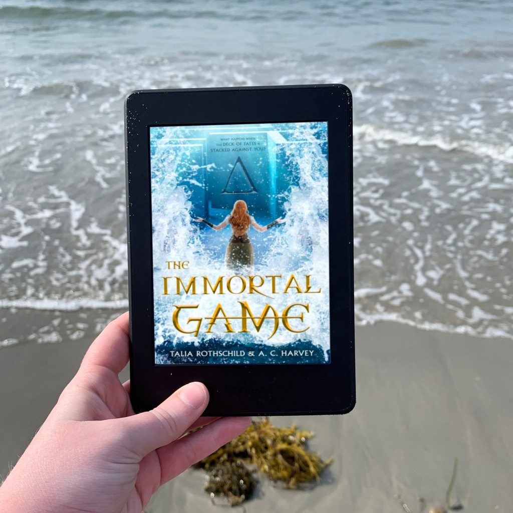 Photo of The Immortal Game ebook on Kindle in front of ocean