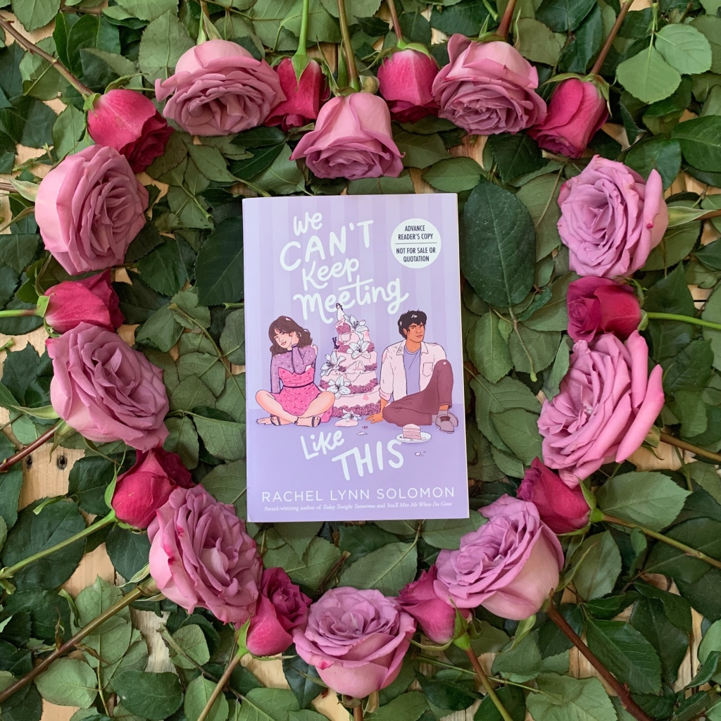 Photo of paperback ARC copy of Rachel Lynn Soloman's We Can't Keep Meeting Like This surrounded by a heart of roses