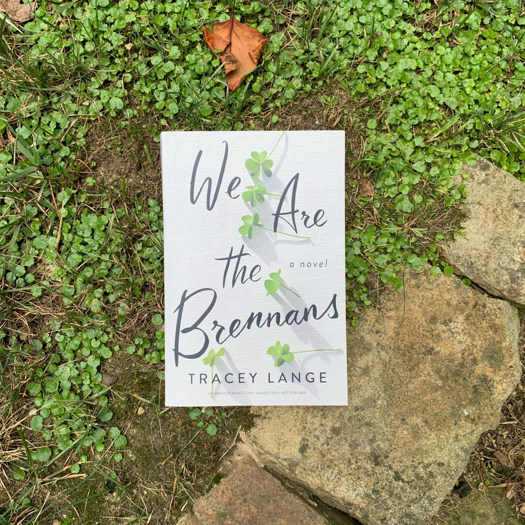 Photo of Tracey Lange's We Are The Brennans, paperback ARC copy on greenery